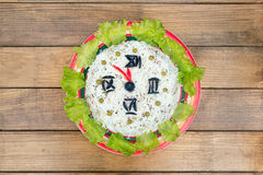 The Christmas salad rice olives greens peas - concept New year clock face, midnight, brown wooden background. Royalty Free Stock Photos