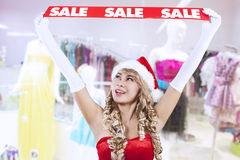 Christmas sale banner by Mrs Claus at mall. Mrs Claus is holding a red SALE banner at the mall Royalty Free Stock Photo