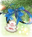 Christmas sale. Blue ribbon, bow with a discount coupon and fir tree branches on a sparkling  holiday background. Festive Christmas background Royalty Free Stock Image