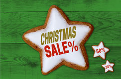 Christmas Sale cinnamon star on green wood background Stock Image