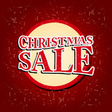 Christmas sale in circular red banner over old paper background Royalty Free Stock Photos