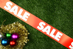 Christmas Sale Concept. Christmas ornament on the green grass background. Christmas sale concept stock image