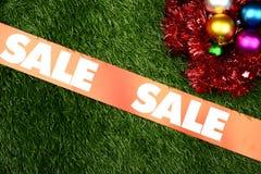 Christmas Sale Concept. Christmas ornament on the green grass background. Christmas sale concept royalty free stock photography