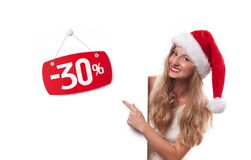 Christmas sale. Beautiful woman in santa hat pointing at sale Stock Photos