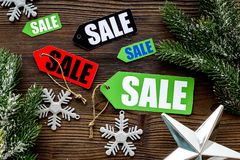Christmas sale. Sale labels near spruce branch and xmas decor on wooden background top view Stock Photography