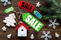 Christmas sale. Sale labels near spruce branch and xmas toys on wooden background top view Stock Image