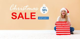 Christmas sale message with woman with Santa hat holding a shopping bag royalty free stock photos