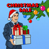 Christmas Sale. Pop Art Man in Santa Hat with Gifts and Christmas Tree Royalty Free Stock Photos