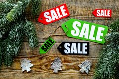 Christmas sale. Sale labels near spruce branch and xmas decor on wooden background top view Stock Photo