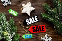 Christmas sale. Sale labels near spruce branch and xmas decor on wooden background top view Royalty Free Stock Photo