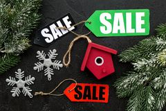 Christmas sale. Sale labels near spruce branch and xmas toys on black background top view Royalty Free Stock Images