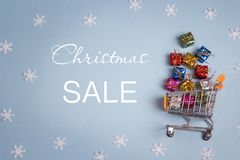 Christmas sale and shopping trolley with gift boxes. Stock Image