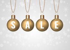 Christmas sale sign on golden baubles over white background Royalty Free Stock Images