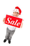 Christmas Sale Time. Standing child holding a sale sign up high suitable for pre or post Christmas sales Royalty Free Stock Image