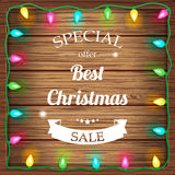 Christmas sale on wooden background with christmas lights. Vector Stock Photography