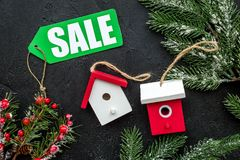 Christmas sale. Word sale on green label near xmas toys and spruce branch on black background top view Royalty Free Stock Photo