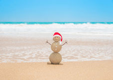 Christmas sandy snowman in santa hat at tropical beach Stock Image