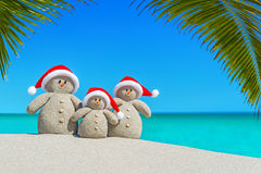 Christmas sandy Snowmen family in Santa hats at palm beach. Royalty Free Stock Photography