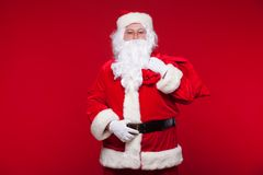 Christmas. santa claus with big bag on shoulder is on red background.  Royalty Free Stock Photo