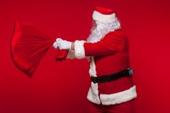 Christmas. santa claus with big bag on shoulder is on red background.  Stock Images