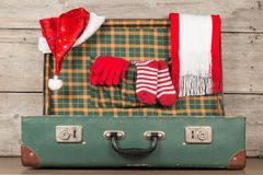 Christmas Santa Claus Caps and Knitting Strips Golfs in Open Wooden Suitcase. Christmas accessories in a suitcase for travel Stock Photo