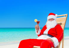 Christmas Santa Claus with cocktail on sunlounger at tropical be. Christmas Santa Claus resting on sunlounger with fresh juice cocktail at ocean sandy tropical Stock Images