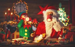 Christmas. Santa Claus with Elf Drink Milk and Eat Cookies Royalty Free Stock Images