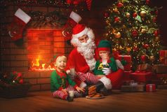 Christmas. Santa Claus with Elves Drink Milk and Eat Cookies Royalty Free Stock Photo