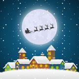 Christmas Santa Claus flying on a Sleigh Over the Winter Village Royalty Free Stock Photos