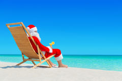 Christmas Santa Claus with fresh juice on sunlounger at tropical. Claus relax on wooden sunlounger with fresh orange juice cocktail at ocean tropical sandy Royalty Free Stock Images