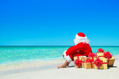 Christmas Santa Claus with gift boxes relaxing at ocean beach. Christmas Santa Claus with golden gift fancy boxes relax at ocean tropical beach sand - New Year stock photo