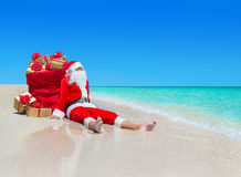 Christmas Santa Claus with gift boxes sack at tropical beach. Christmas Santa Claus with golden gift boxes sack with red bows resting at ocean tropical sandy Royalty Free Stock Image