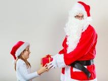 Christmas Santa Claus giving girl present Stock Image