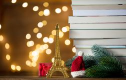 Christmas Santa Claus hat with Eiffel tower and pile of books. With fairy lights on background royalty free stock photos