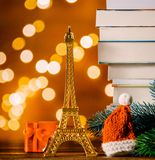 Christmas Santa Claus hat with Eiffel tower and pile of books. With fairy lights on background stock photos
