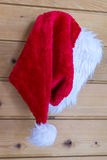 Christmas Santa Claus hat hanging on a peg. Festive red Christmas Santa Claus hat hanging on a peg on a wooden wall in a seasonal concept Royalty Free Stock Photos