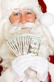 Christmas: Santa Claus Holds Fanned Out US Money Stock Photo