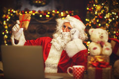 Christmas. Santa Claus with laptop reading letter Royalty Free Stock Photography