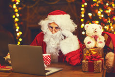 Christmas. Santa Claus with laptop reading letter. Christmas. Santa Claus with a laptop reading a letter and drinking tea Stock Images