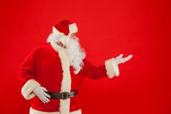 Christmas. Santa Claus pointing in blank a place, red background. Santa Claus pointing in blank a place, red background. Merry Christmas royalty free stock image