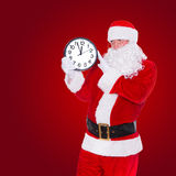 Christmas Santa Claus pointing at clock showing five minutes to midnight. On red background. Happy New Year concept stock photo