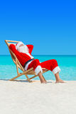 Christmas Santa Claus relax in deckchair at ocean sandy beach Royalty Free Stock Photos