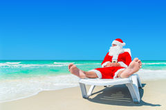 Christmas Santa Claus relax on sunlounger at ocean tropical beach. Santa Claus relax on sunlounger at ocean tropical sandy beach. Meкry Christmas and Happy New Royalty Free Stock Photos