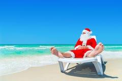 Christmas Santa Claus relax on sunlounger at ocean tropical beach Royalty Free Stock Photos