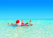 Christmas Santa Claus relax swimming in ocean turquoise transparent water. stock photos