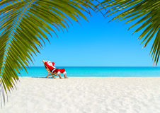 Christmas Santa Claus relaxing on sunlounger at ocean sandy tropical beach. Under palm leaves. Happy New Year travel destinations to hot countries concept Stock Image