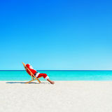 Christmas Santa Claus relaxing in sunlounger at ocean tropical b. Santa Claus relaxing in sunlounger at ocean tropical sandy beach - Christmas and New Year Royalty Free Stock Photo