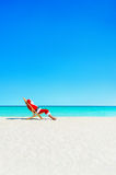 Christmas Santa Claus relaxing in sunlounger at ocean tropical b. Santa Claus relaxing in sunlounger at ocean tropical sandy beach - Christmas and New Year Royalty Free Stock Image