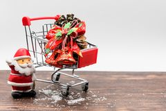 Christmas santa claus and shopping concept. X& x27;Mas red santa claus, bell, Pine cones, snow on red small shopping cart on old wood table and white background Royalty Free Stock Photography