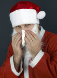 Christmas santa claus sneezing into tissue Stock Images